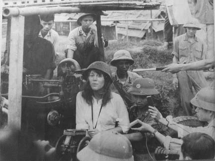 Jane Fonda mirthfully posing with enemy North Vietnamese soldiers