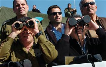 Israel's Defense Minister Amir Peretz (right) looks through binoculars with the lens cap on. On the left is the army's new Chief of Staff, Lt. Gen. Gabi Ashkenazi. They're reviewing a military drill in the Golan Heights. <font size=-2>(Source: msnbc.com)</font>