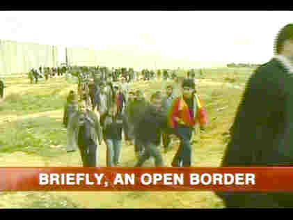 Gazans pour through hole blasted in border wall with Egypt. <font face=Arial size=-2>(Source: BBC)</font>