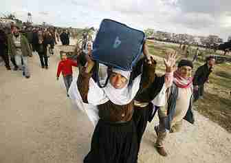 Euphoric Gazans carry goods back to Gaza from Egypt. <font face=Arial size=-2>(Source: Der Spiegel)</font>