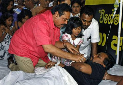 Sri Lanka's President Mahinda Rajapaksa offers a glass of water to his Housing Minister Wimal Weerawansa to end his hunger strike <font face=Arial size=-2>(Source: VOA)</font>