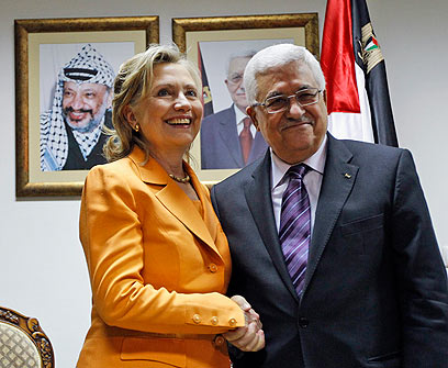 Mahmoud Abbas shakes hands with Hillary Clinton.  In the back is a picture of Yasser Arafat (Ynet)