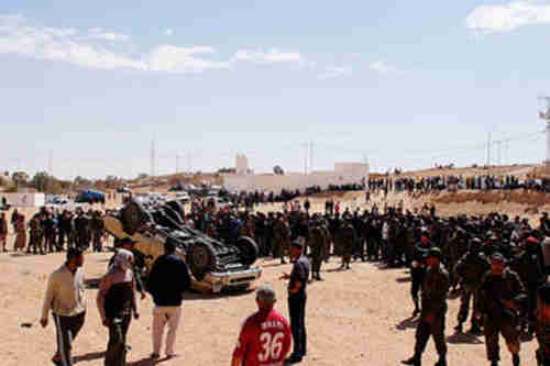 In Dehiba, people gather around overturned car belonging to Libyan army (CS Monitor)