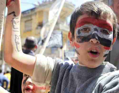 A Lebanese child with a Syrian flag painted on his face, and the phrase 'Bring down the regime' written on his hand, in solidarity with Syria's protesters (Xinhua)