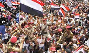 Yemeni army soldiers lifted by anti-government protesters, celebrate Saleh's departure (AP)