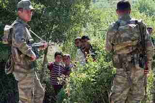 Turkish soldiers guard border as Syrian refugees await authorization to enter (AP)