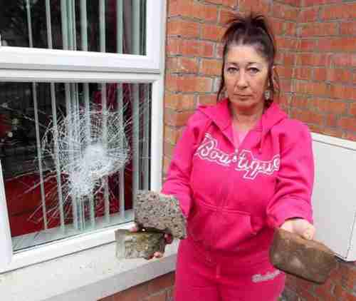 Belfast resident Anne-Marie Shanks beside windows that were smashed (Belfast Telegraph)