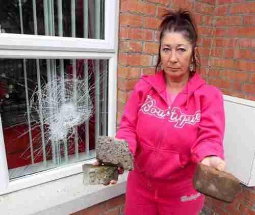 Belfast resident Anne-Marie Shanks beside windws which were smashed (Belfast Telegraph)