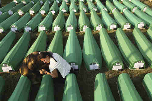 Two young women on Saturday mourn over one of 613 coffins of Srebrenica massacre (Getty)