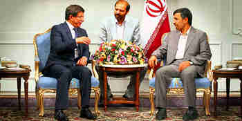 Turkish Foreign Minister Ahmet Davutoglu (L) talks to Iranian President Mahmoud Ahmadinejad