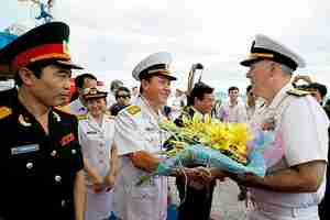 Col. Nguyen Van Lam, center, greets U.S. Rear Admiral Tom Carney with flowers on Friday (Reuters)