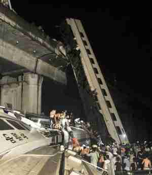 Wreckage of train after two carriages fell off a bridge (AP)