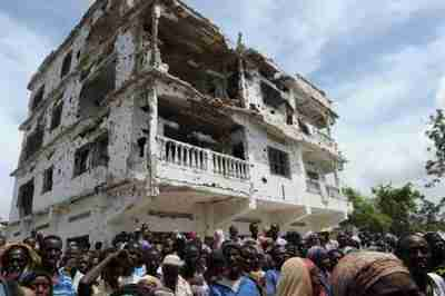 A group of internally displaced people crowd underneath a partially destroyed building in Mogadishu on Sunday (AFP)