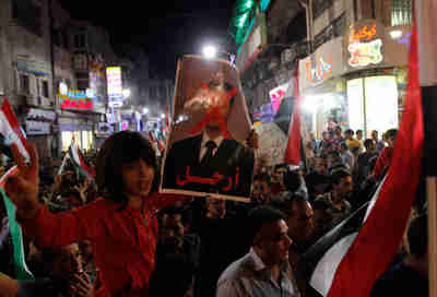 Palestinian girl in Ramallah holds poster depicting Assad with a red 'X' across his face. (Reuters)