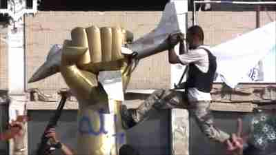 Rebel fighter tears down the iconic giant golden hand crushing a US fighter jet (BBC)