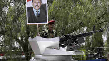 A Yemeni soldier holds up a picture of President Ali Abdullah Saleh during a rally in support of his regime on Friday (CNN)