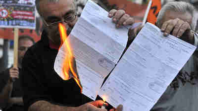 Members of the 'we won't pay' movement in Athens burn their tax bills (AFP)