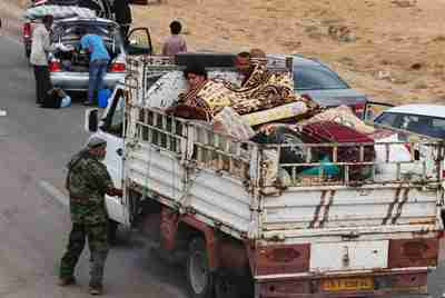 Civilians fleeing Sirte pass a checkpoint on the outskirts of the city on Sunday. (Reuters)