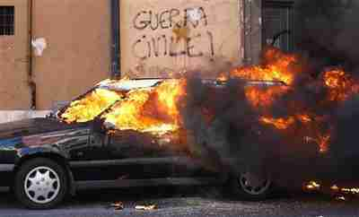 A car burns next to a wall with graffiti reading 'Civil War' on Saturday in Rome (Reuters)