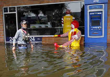 A Thai resident wades past Ronald McDonald in Bangkok (EPA)