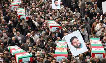 Iranians carry honorary coffins and pictures of Hassan Tehrani Moghaddam in a funeral procession (Reuters)