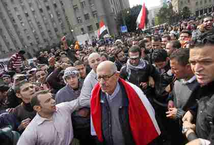 Pro-reform candidate and Nobel Peace Prize laureate Mohamed ElBaradei, draped in an Egyptian flag, is surrounded by protesters as he arrives for Friday prayers in Tahrir Square in Cairo. (AP)