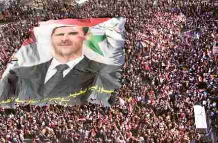 Pro-Syrian regime protesters carry a huge portrait of President Bashar Al Assad during a demonstration to show their solidarity in Damascus (AP)
