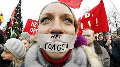 A protester with her mouth taped shut against Putin.  The words read 'No vote' (AP)