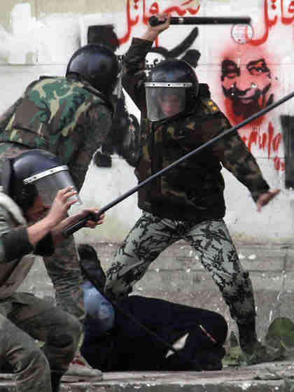 In Tahrir Square, soldiers beating a veiled woman protester