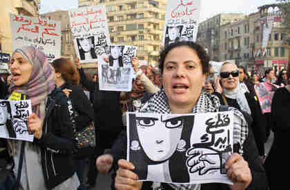 Women at Tuesday's march carrying banners depicting a woman's face and the arm of a soldier that reads, 'Your hand should be cut off' (Ahram)
