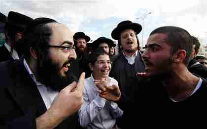 An ultra-Orthodox Jewish man argues with a secular man during the protests (Reuters)