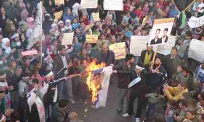 Anti-government protesters burn an image of President Bashar al-Assad during a demonstration in Homs. (Reuters)