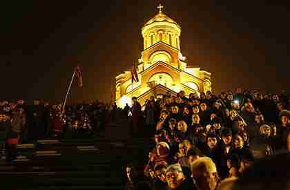 Georgians attend Orthodox Christmas celebrations at the Holy Trinity Cathedral in Tbilisi, early Saturday (AP)