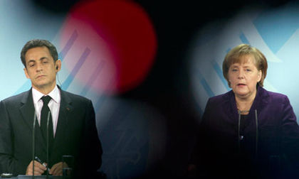 Nicolas Sarkozy and Angela Merkel at a press conference on Monday (AP)