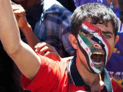 Anti-government protester in Yemen with the colors of the national flags of Yemen and Syria on his face (Reuters)