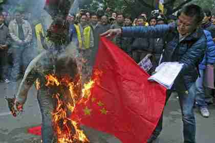 Tibetan exiles burn a Chinese flag and an effigy representing a Chinese official during a protest in New Delhi, January 17, 2012 (Reuters)