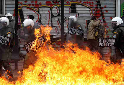Protesters with riot police in Athens on Friday (EPA)