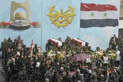 Snow falls as Syrian soldiers carry coffins of their colleagues during a funeral ceremony in Damascus Saturday (Reuters)