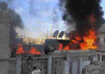 Flames rise from a house shelled by army in Baba Amr neighborhood in Homs (AP)