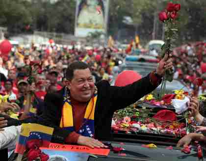 Hugo Chávez holds up flowers thrown by supporters in Caracas, just before he leaves for cancer surgery in Cuba (AP)