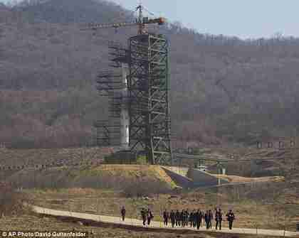 A group of journalists walk down a road in front of North Korea's Unha-3 rocket which it is expected to fire in the middle of April (AP)