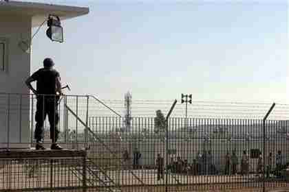 A guard watches over illegal immigrants inside a newly-built detention camp