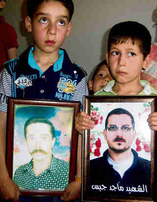Syrian children holding portraits of their fathers, killed on Saturday by pro al-Assad forces (Reuters)