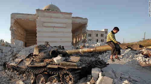 A boy plays on the gun of a destroyed Syrian army tank partially covered in the rubble of the destroyed Azaz mosques north of Aleppo (CNN)