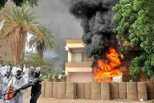 Sudanese policemen stand guard after protesters attacked the German and British embassies in Khartoum