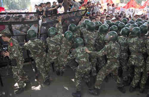 Chinese paramilitary police try to prevent demonstrators from breaking through a fence set up outside the Japanese Embassy in Beijing (AP)