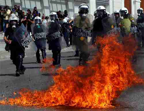 A molotov cocktail explodes beside riot police officers near Syntagma square in Athens. (Reuters)