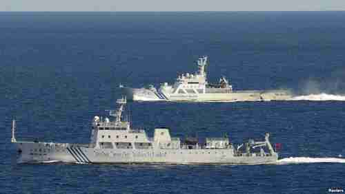 Chinese surveillance ship in front, Japanese coast guard ship in back (Kyodo)