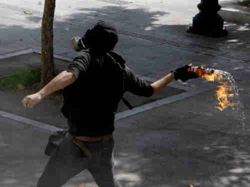 Protester throws petrol bomb at police (Reuters)
