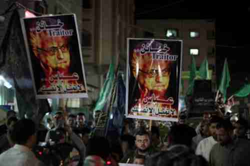 Hamas supporters carry signs calling Abbas a 'traitor'